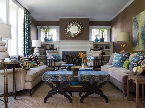 A small-scale animal print on the stools and neutral stripe on the armchair cushions balance the bold, graphical prints of the throw pillows and curtains in this colorful, contemporary living room. The color palette of deep blues, lime green and chocolate brown offers a modern twist to the traditional architectural features of the space.