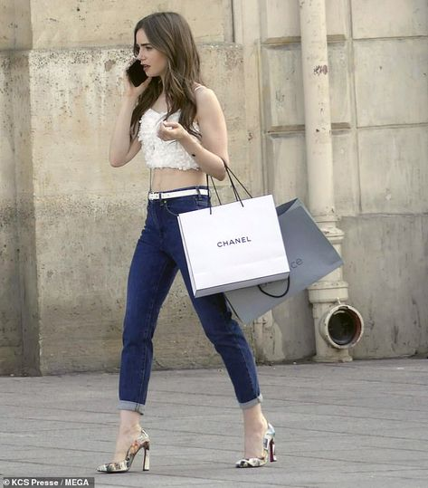 Lily Collins flashes her midriff in a white feathered crop and jeans