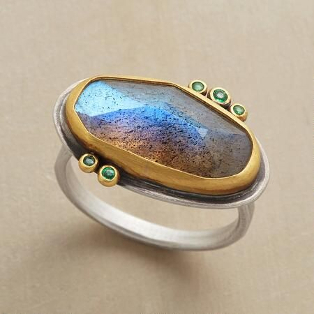 Emerald Dotted Ring: An emerald, labradorite and gold ring, wherein gleaming emeralds dot the irregular perimeter of faceted labradorite, the stones set in gold on a sterling silver band. Handmade in USA by Ananda Khalsa. Whole sizes 5 to