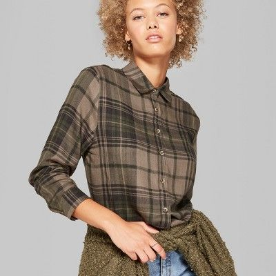 9613654c627a3 Camo long-sleeve shirt comes in dark green and has a full button-up front.  Features a slightly frayed hem and chest pocket. Finished with a Tok…