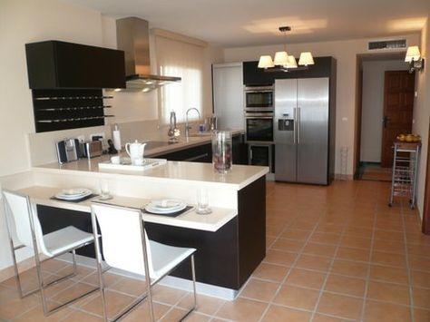 Cocina en blanco y negro, con pequeño espacio para comer y electrodomésticos de acero