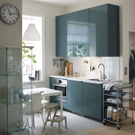 A small, modern kitchen with white walls and high-gloss gray-turquoise doors.