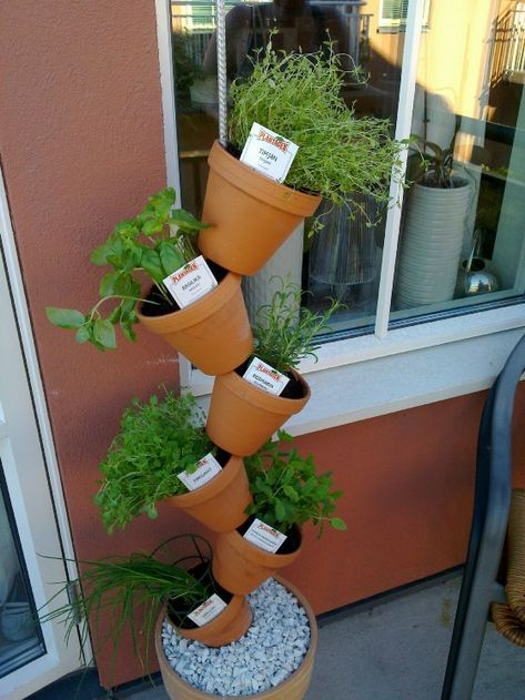 Big pot with a steel rod held in place by pebbles (making a permanent solution with concrete might be more stable). Threaded terracotta pots on the rod and planted herbs in them.