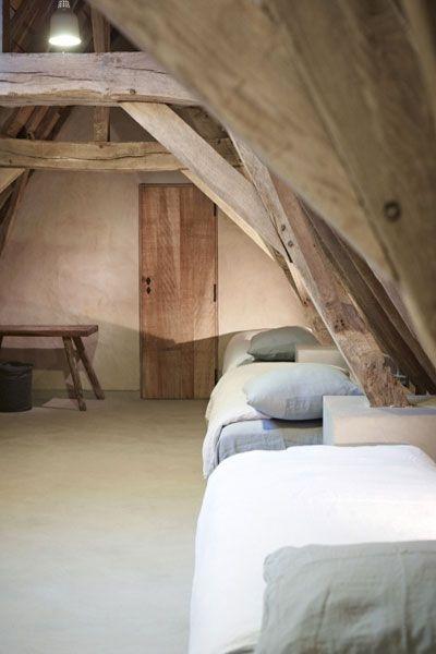 sol béton , mur béton et charpent en bois brut , enfilade de lit