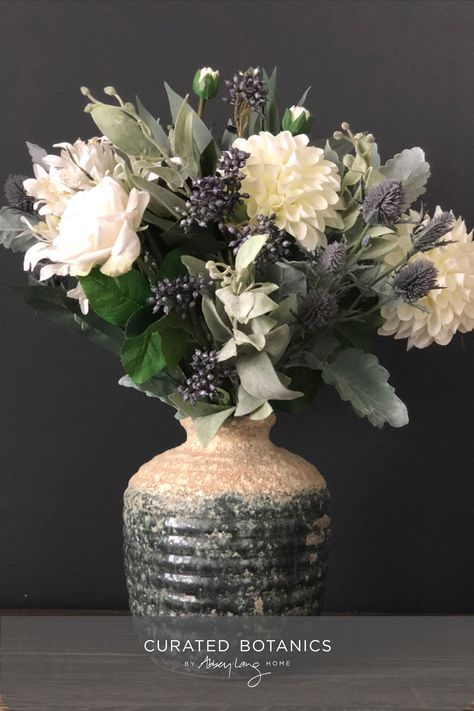 White roses, dahlia, and agapanthus sit amongst an eclectic mix of seeds, thistles, grasses and foliage for a pretty, wintery vibe. The two-tone 'aged look' round urn is solid (heavy) and looks great from all angles. #curatedbotanics #artificialflowers #mothersdaygiftideas #vasearrangement