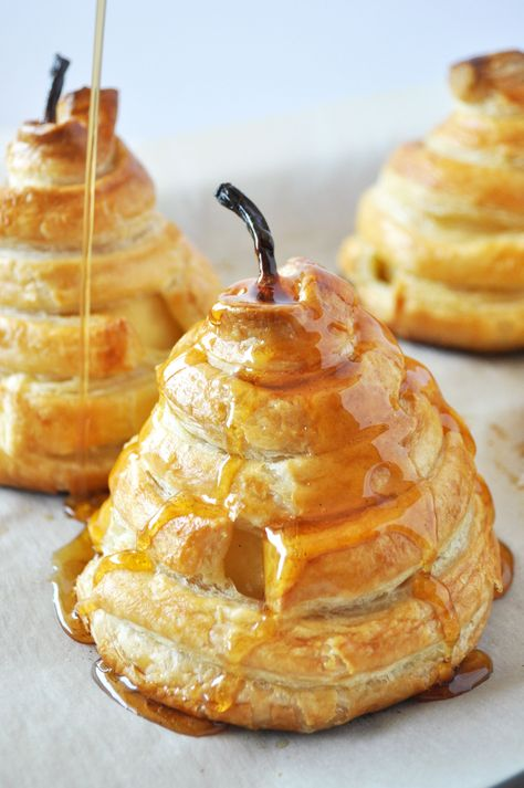 These Honey-Poached Pears in Puff Pastry are deceptively easy, but will impress any dinner guests. A flavor-packed poaching liquid infuses pears with warm spices, then later becomes a delectable syrup for drizzling. The pears then get wrapped in puff pastry, sealing in all of that delicious flavor, and adding a flaky crunch. #recipe #summerrecipe