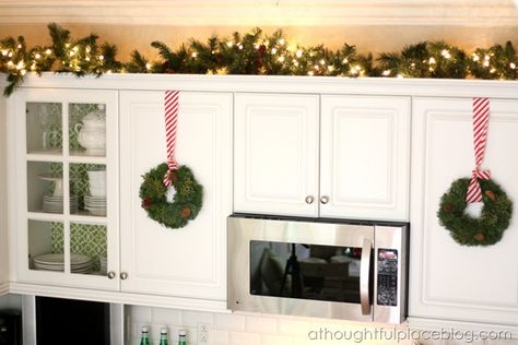 lights and greenery above the kitchen cabinets & wreaths hanging from pretty ribbon on the cabinets