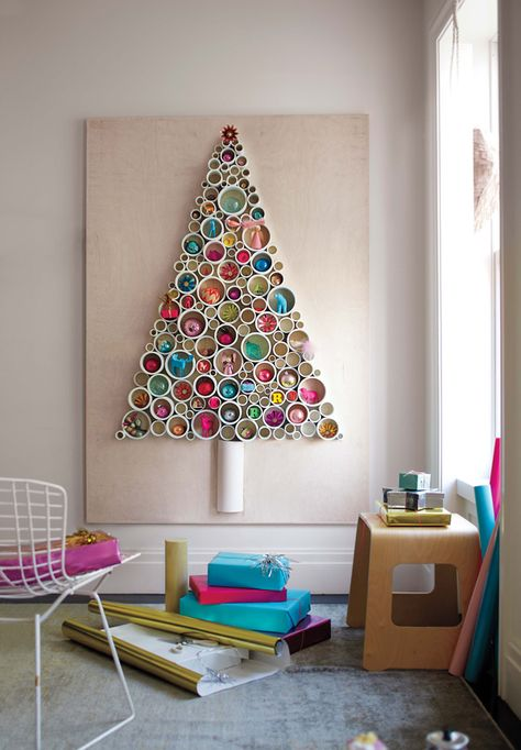 PVC Christmas tree wall art ~ This unique Christmas Tree creation is a fun way to display leftover Holiday ornaments & trinkets & it's perfect for small spaces (like my tiny apartment!). All you need to create this seasonal masterpiece are different size PVC pipes cut into rings & a reclaimed piece of wood to mount your creation on! ~ LOVE it! ~ ♥