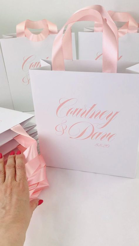 Blush wedding favor bags with satin ribbon handles and your names, Elegant wedding welcome bags for guests. #welcomebox #giftbags #giftbox #personalizedgifts #weddingfavor #weddingwelcomebags #welcomebags #weddingfavorideas  #weddingparty #weddingfavorideas #weddingparty #weddingfavour #weddingwelcome #elegantwedding #mintwedding #weddingfavour #blushwedding