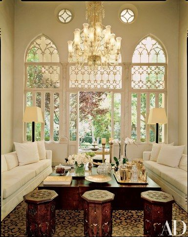 Gothic arches at one end of the living area look out to the property's walled garden. An antique Ottoman chandelier, one of four in the house, draws the eye up to the room's 20-foot ceilings | archdigest.com