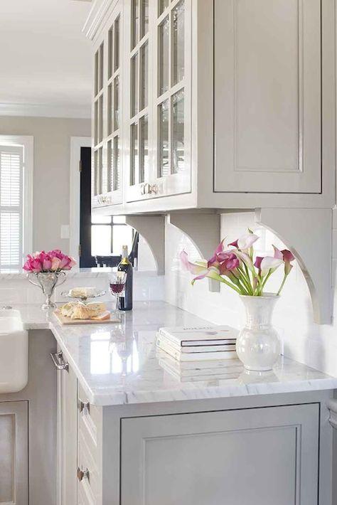 inset white cabinets, corbels (brackets) under upper glass cabinets on backsplash.