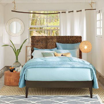 a creative way to decorate around an off-centered window behind the bed