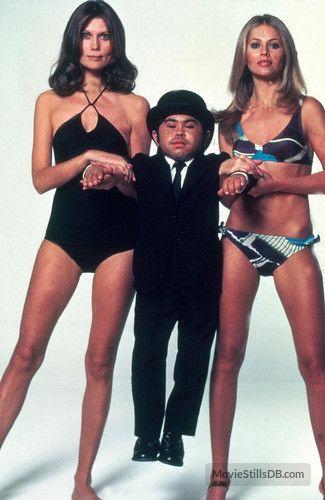 007 #09 1974 ••The Man with the Golden Gun•• BondGirl: Britt Ekland (R, Swede) as Goodnight & Maud Adams as Andrea (L, Swede) + Hervé Villechaize as Nick Nack • Bond: Roger Moore (2nd)