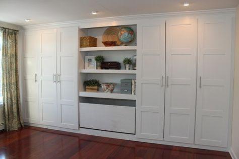 2 armoires de chaque côté et au centre un meuble pouvant accueillir une télévision,  éventuellement dissimulée derrière  des portes coulissantes