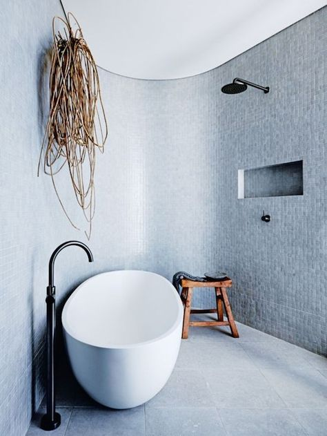 Oval shaped bath tub and curved walls in the bathroom of a dreamy urban beach home. Photo - Anson Smart.