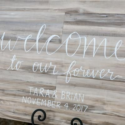 Light washed wooden entrance sign with white cursive font