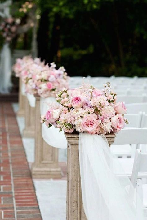 Lining your aisles with pink florals and white tulle is such a romantic touch / http://www.himisspuff.com/outdoor-wedding-aisles/8/