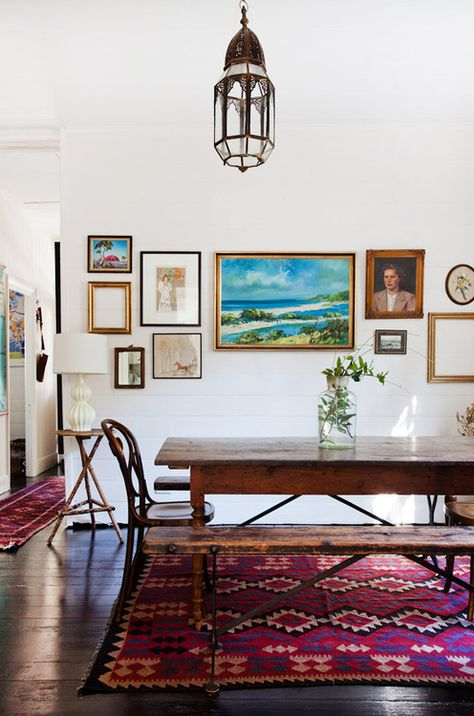 eclectic dining room with rustic dining table and benches, mix of art work, kilim rug, vintage chandelier