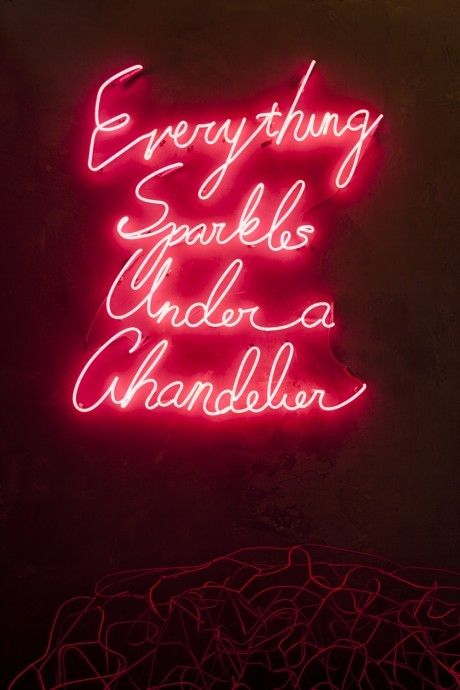Neon pink lights that say everything sparkles under a chandelier ...