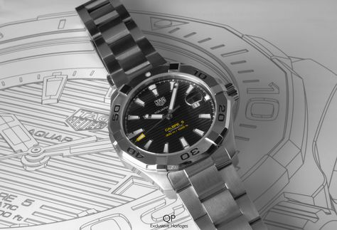 How about the timeless diver watch by TAG Heuer: the Aquaracer Calibre 5! A black and steel beauty that's both stylish and up to task underneath the water surface. The legible dial is well laid out and aimed to be as clear as possible. The hand-applied polished and faceted indexes are provided with luminescent markers, as are the hours, minutes and seconds hands. The seconds hand, additionally, is accentuated in the contrasting orange color, providing a striking appearance.