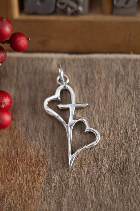 Sterling silver hearts connected by the cross. A beautiful symbol of the bond we have with others because of God's love for us. - Pendant measures: 1 x - Create a necklace by adding any chai