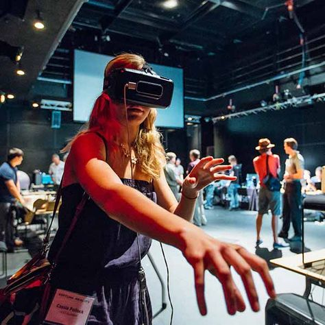 """Image: A conference attendee tests a virtual reality headset at the """"Future of Virtual Reality"""" confere"""