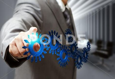 Photograph: Business man hand point cogs icons in board room #12248087