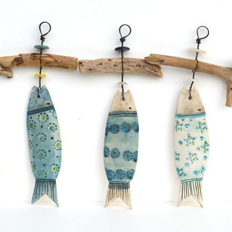 Each ceramic fish and driftwood hanger is lovingly handmade by Shirley Vauvelle .