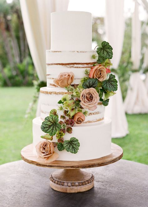 A vine of earthy flowers and vivid greenery dress up frosted tiers and seminude layers. The look is perfect for a safari or bohemian themed summer or fall wedding! Click through for more simple wedding cake ideas! #simpleweddingcakes #safariwedding #bohowedding #bohoweddingcake #weddingcakeideas