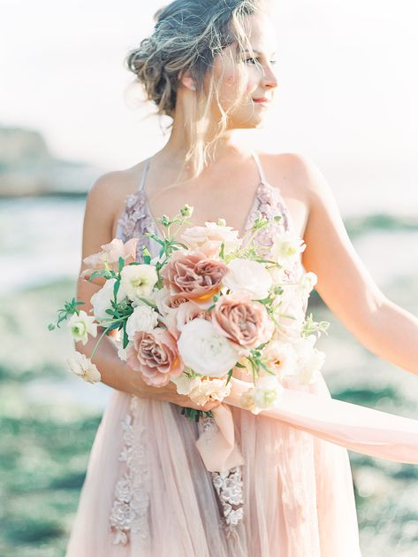 Beautiful free flowing garden style wedding bouquet held by Bride in a blush wedding dress on the beach at Sunset Cliffs in San Diego CA. Bouquet created by San Diego wedding florist, Le Champagne Projects