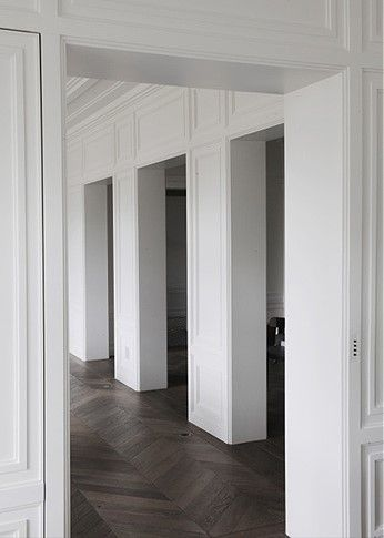 Warm wooden parquet offsets Haussmanian painted moulding: Neuilly apartment by Joseph Dirand.
