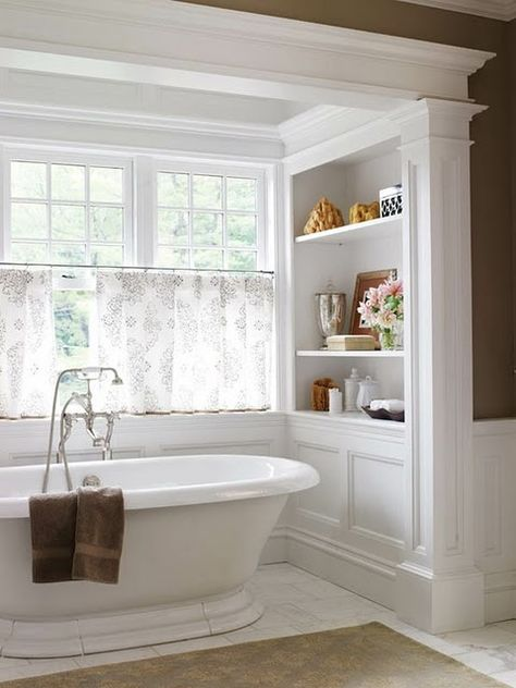 What could be better than a deep soaking tub positioned in front of a window and flanked by shelves to house decorative accessories or linens?