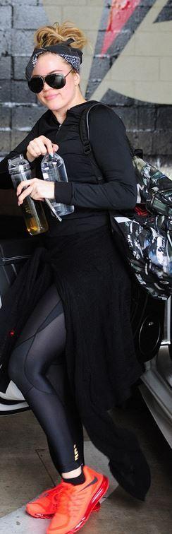 336d5573bf2a7 Who made Khloe Kardashian's black backpack, aviator sunglasses, and orange  sneakers?