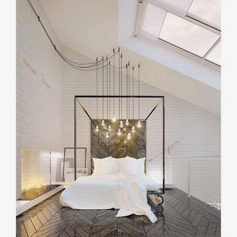 minimalist bedroom in brick loft with chevron floors and Edison bulb chandelier