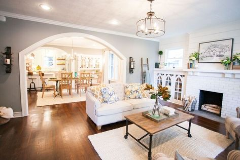 Love the large arched openings between living areas, the beautiful glass cabinetry on each side of the fireplace, and the all white fireplace with white brick and white shiplap above.