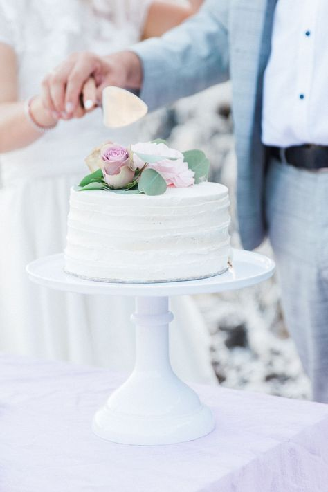 An elopement does not mean you have to miss out on any of the treats! At our Greek island beach elopement in Lefkada, Konstantin and Nadya celebrated their I do by sharing cake and champagne after their ceremony. Single tier, white wedding cake with pastel flowers. By Lefkas Weddings with Maxeen Kim Photography #elopementcake #destinationweddingcake