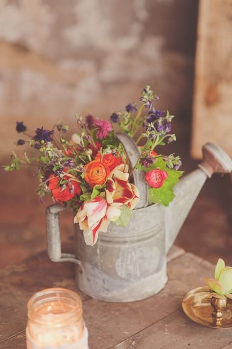 using an old watering can for floral arrangement - love this idea for a wedding breakfast centrepiece at Utopia or a marquee at Eden. Country charm.