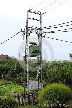 Green electric power transformer with grey metal utility box