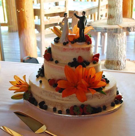 Naked Cake with fresh Strawberries, Blackberries, Raspberries and Blueberries. Oval shape ~ Gorgeous huge Orange Lillies! Top Tier Wedding Cakes - Medford, Oregon