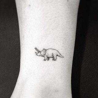 45 Originales Ideas De Tatuajes De Dinosaurios Tatuajes De Arte Corporal Tatuaje De Pulsera En El Tobillo Tatuajes Minimalistas Tatuaje de un dinosaurio con lentes y pipa, tatuaje a color en la pierna. 45 originales ideas de tatuajes de