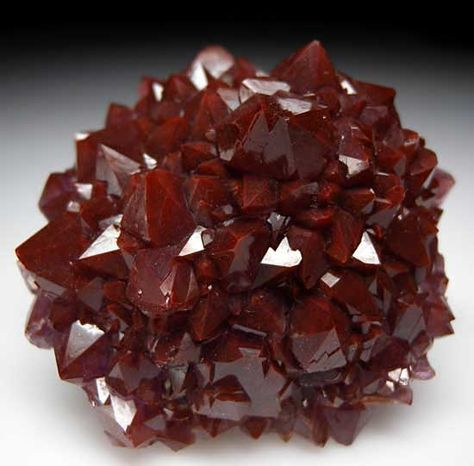 Mound shaped cluster of crystals with deep maroon red surface due to Hematite inclusions (purple underneath).