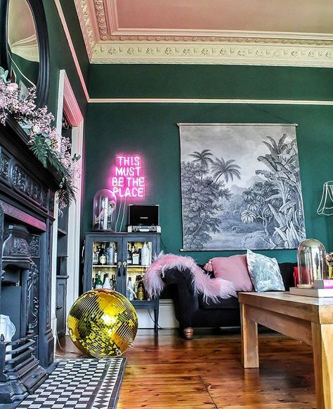 This is The 1882 House's living room, where the are walls painted in Wall Paint in Amsterdam Green and the accessories are bright, bold and witty! We're green with envy over this sophisticated but fun space. Love the mix with fuchsia pink and kitchen accessories. Modern take on a Victorian room.
