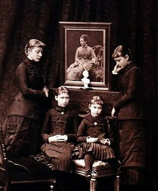 Alix with sisters Victoria, Elizabeth, and Irene. The portrait is of their mother, Princess Alice.