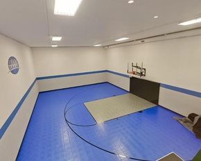 This Home Gym Features Blue And Gray Sport Court Sports Flooring Find Out More About A Sport Cou Home Basketball Court Indoor Basketball Court Basketball Room