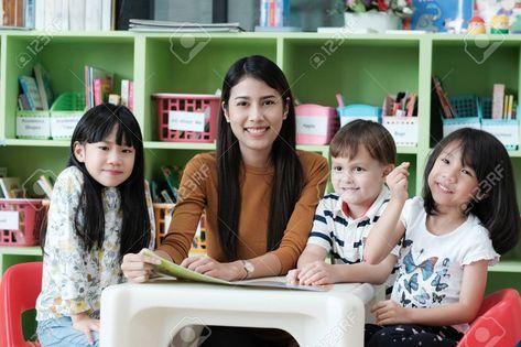 Young asian woman teacher teaching kids in kindergarten classroom,..