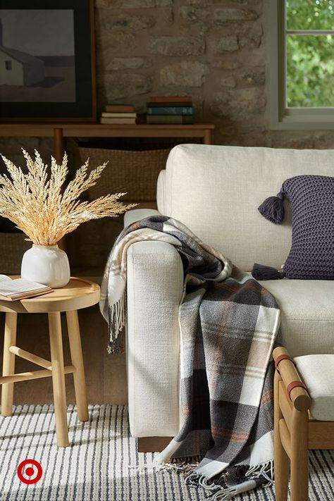 Make your living room fall-ready with a soft plaid throw, cozy knit pillows, and a dried arrangement to bring the outdoors in.