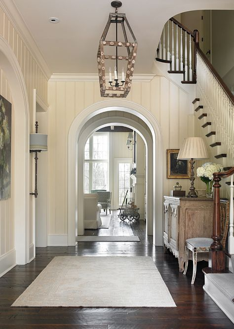 """Traditional Foyer with archway. Foyer. Beautiful foyer with archways and rustic dark hardwood floors.  Floors are 8""""-10"""" wide antique heart pine plank wood floors, dark stained and scraped.  Ceiling paint color: Benjamin Moore Cloud White CC-40.  Lighting: Most lighting used in this home are antique finds. T.S. Adams Studio. Interiors by Mary McWilliams from Mary Mac & Co."""