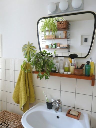 15 Incredible Small Bathroom Decorating Ideas - modern bathroom with white square tiles, bright chartreuse hand towels, pretty green plants and a wooden shelf