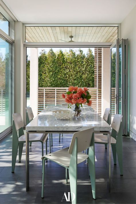 Interior designer Bella Mancini worked with Douglas Wright Architects to craft a contemporary dream home not far from Manhattan. The clients added a patio so that the breakfast nook would have easy outdoor access. The custom dining table is by James Devlin. #patio #outdoors #diningtables #breakfastnook #design #tables #chairs #flowers #florals #windows #glass