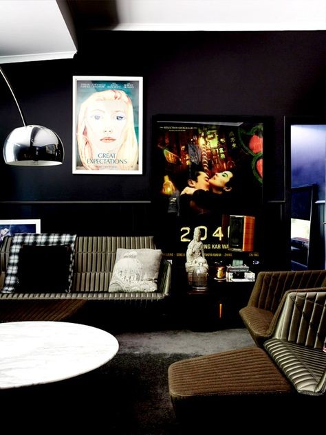 Black living room with oversized artwork and industrial furniture